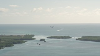 AX0027_037 - 5K stock footage aerial video of tracking an F-18 landing at Naval Air Station Key West, Key West, Florida