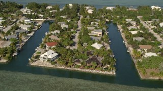 AX0027_050 - 5K stock footage aerial video of approaching homes on the island shore, Lower Sugarloaf Key, Florida