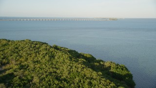 AX0028_017 - 5K stock footage aerial video of flying over mangroves, revealing Overseas Highway bridge, Long Key, Florida, sunset