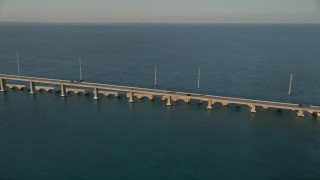 AX0028_021 - 5K stock footage aerial video of tracking light traffic on Overseas Highway bridge at sunset, Craig Key, Florida