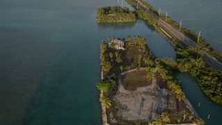 AX0028_022 - 5K stock footage aerial video of approaching a home and tilt down to bird's eye view of it at sunset, Craig Key, Florida