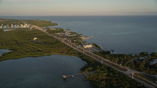 AX0028_023 - 5K stock footage aerial video of Overseas Highway by Drop Anchor Resort and Marina, Islamorada, Florida, at sunset
