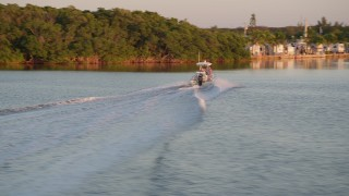 AX0028_032 - 5K stock footage aerial video of a fishing boat racing past mangroves at sunset, Key Largo, Florida