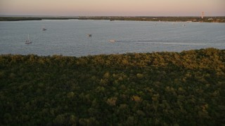 AX0028_033 - 5K stock footage aerial video of flying over mangroves, approaching sailboats and fishing boat at sunset, Key Largo, Florida