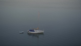 AX0028_038 - 5K stock footage aerial video of approaching a sailboat near the shore at sunset, Key Largo, Florida