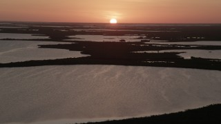 AX0028_046 - 5K stock footage aerial video ascend over the Overseas Highway, reveal mangroves, bays, Key Largo, Florida, sunset