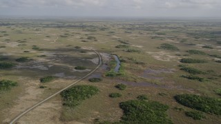 AX0030_057 - 5K stock footage aerial video of flying over a winding country road, Florida Everglades, Florida