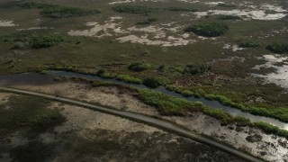AX0030_058 - 5K stock footage aerial video of flying by country road and marshland, Florida Everglades, Florida