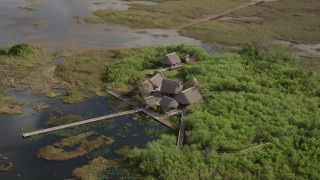 AX0030_061 - 5K stock footage aerial video of orbiting huts and dock on marshland, Florida Everglades, Florida