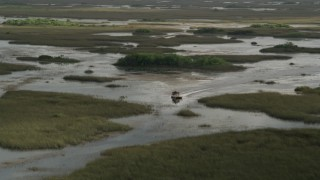 AX0030_063 - 5K stock footage aerial video of tracking a fanboat racing through marshland, Florida Everglades, Florida