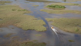 AX0030_064 - 5K stock footage aerial video of tracking a fanboat racing through marshland, Florida Everglades, Florida