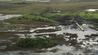 AX0030_066 - 5K stock footage aerial video of tracking a fanboat near dock, Florida Everglades, Florida