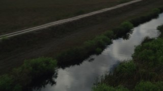 AX0030_099 - 5K stock footage aerial video fly over marshland, reveal river, country road, Florida Everglades, Florida