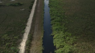 AX0030_103 - 5K stock footage aerial video of following river, country road through Florida Everglades, Florida