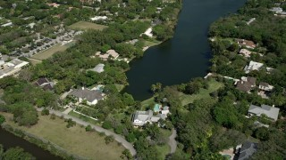 AX0031_002 - 5K stock footage aerial video approach residential neighborhood, tilt down to shore of lake, Coral Gables, Florida