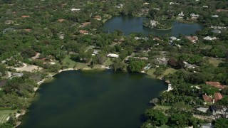 AX0031_003 - 5K stock footage aerial video of flying over a lake toward homes on the shore, Coral Gables, Florida