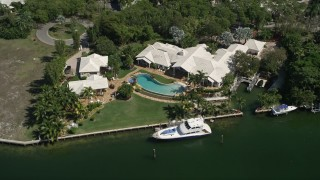 AX0031_010 - 5K aerial stock footage video of approaching mansion by canal in Coral Gables, Florida