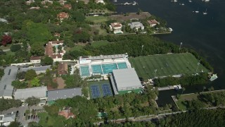 AX0031_014 - 5K stock footage aerial video approach Ransom Everglades School, sports fields, pools, Coconut Grove, Florida