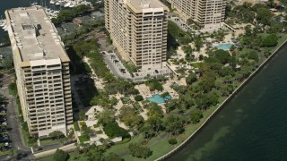 AX0031_017 - 5K stock footage aerial video of flying by condo complexes with pools, Grove Isle, Florida