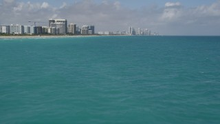 AX0031_067 - 5K stock footage aerial video of flying over the Atlantic Ocean, revealing beachfront buildings, Sunny Isles Beach, Florida