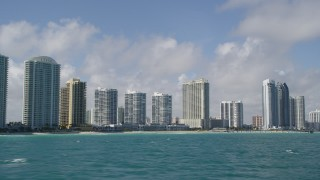 AX0031_076 - 5K stock footage aerial video of flying by condominium complexes on the shore, Sunny Isles Beach, Florida