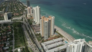 AX0031_085 - 5K stock footage aerial video of approaching condominium complex on shore, tilt down, Sunny Isles Beach, Florida