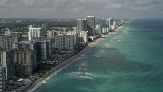 AX0031_089 - 5K stock footage aerial video of following beach, approaching condominium complex, Hallandale Beach, Florida