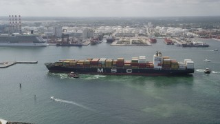 AX0031_103 - 5K stock footage aerial video of approaching tugboats turning cargo ship, Port Everglades, Fort Lauderdale, Florida