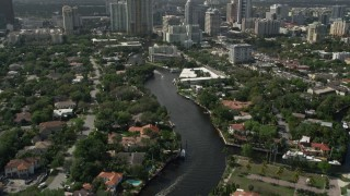 AX0031_113 - 5K stock footage aerial video of following New River past mansions, revealing Downtown Fort Lauderdale, Florida