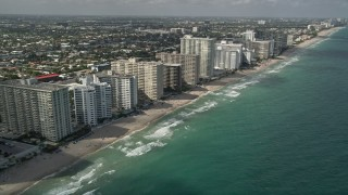 AX0031_143E - 5K stock footage aerial video of flying by apartment buildings, revealing beach, coastline, Fort Lauderdale, Florida