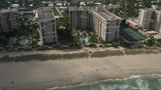 AX0031_147 - 5K stock footage aerial video of flying by apartment buildings, sunbathers, Lauderdale by the Sea, Florida