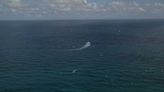 AX0031_180 - 5K stock footage aerial video of following speedboat cruising on the Atlantic, Pompano Beach, Florida