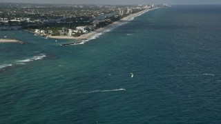 AX0031_181 - 5K stock footage aerial video of flying over kite surfers near Hillsboro Inlet Light, Hillsboro Beach, Florida