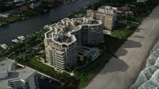 AX0032_011 - 5K stock footage aerial video of following the beach, tilt down to condominium complex, Hillsboro Beach, Florida