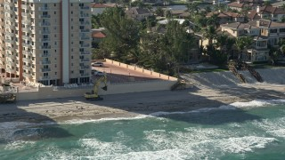 AX0032_033 - 5K stock footage aerial video of flying by construction equipment on the beach, Highland Beach, Florida