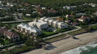 AX0032_050 - 5K stock footage aerial video of flying by a condominium complex by the shore, Ocean Ridge, Florida