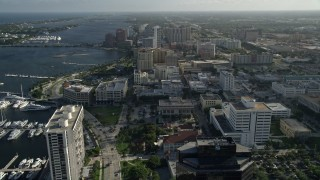 AX0032_085 - 5K stock footage aerial video of panning across office buildings, revealing boats docked, West Palm Beach, Florida