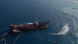 AX0032_111 - 5K stock footage aerial video of orbiting a dredging ship near the coast, Palm Beach Shores, Florida