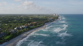 AX0032_125 - 5K aerial stock footage video of following the coast past homes and beach, North Palm Beach, Florida