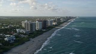 AX0032_128 - 5K stock footage aerial video of following the beach, approaching condominium complexes, Juno Beach, Florida