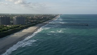 AX0032_131 - 5K stock footage aerial video of following the beach, approaching the pier, Juno Beach, Florida