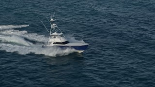 AX0032_144 - 5K stock footage aerial video of tracking a fishing boat racing across the Atlantic, Jupiter, Florida
