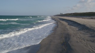 AX0032_147 - 5K stock footage aerial video of flying low over waves lapping the beach, Hobe Sound, Florida