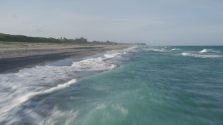 AX0032_149 - 5K stock footage aerial video fly over Atlantic Ocean, revealing waves lapping the beach, Hobe Sound, Florida