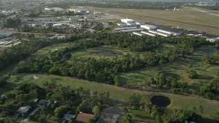 AX0032_162 - 5K stock footage aerial video of flying by Martin County Golf and Country Club, tilt down on pond, Stuart, Florida