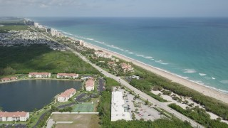 AX0033_010 - 5K stock footage aerial video fly by condominium complexes toward the beach, Jensen Beach, Florida