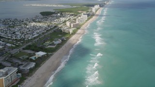 AX0033_011 - 5K stock footage aerial video of following apartment buildings on the beach and blue waters, Jensen Beach, Florida