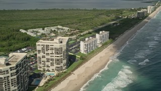 AX0033_014 - 5K stock footage aerial video of fly by beachside apartment buildings, Jensen Beach, Florida