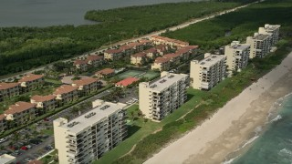 AX0033_018 - 5K stock footage aerial video of following the beach blue waters toward vacation rentals, Jensen Beach, Florida