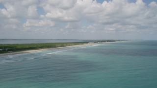AX0033_023 - 5K stock footage aerial video tilt up from blue ocean waters revealing the coast, Fort Pierce, Florida